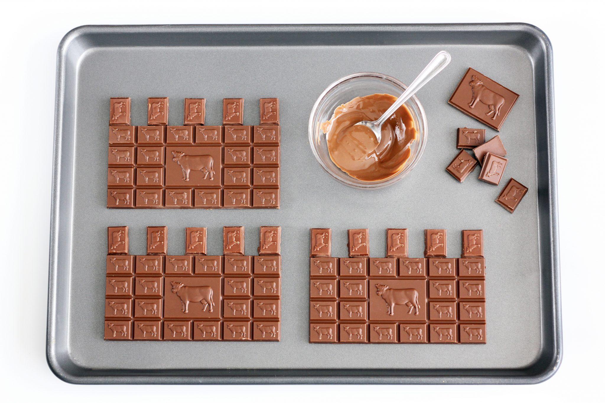 עוגת יום הולדת טירה - עיטור, מניחים על תבנית מרופדת בנייר אפייה 4 חפיסות שלמות של שוקולד חלב, עבור הקירות.